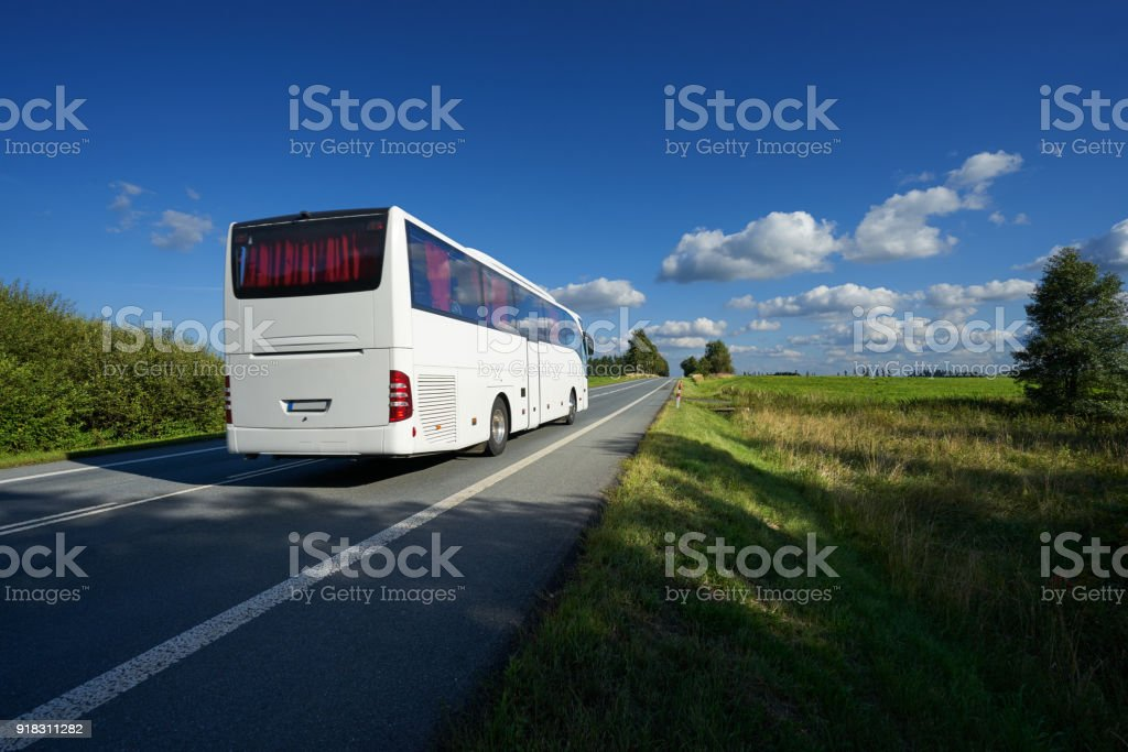 White bus traveling on asphalt road in landscape on a sunny day with blue sky and white clouds stock photo