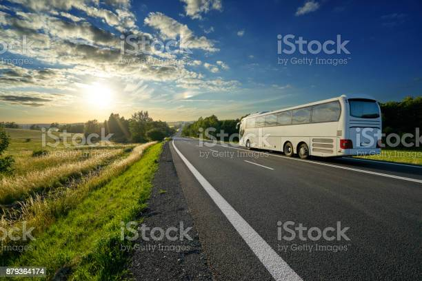White bus traveling on the asphalt road in a rural landscape at sunset