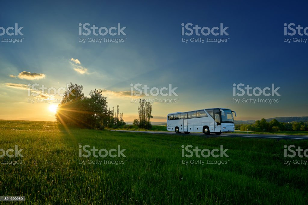 White bus traveling on the road between green meadows in a rural landscape at sunset stock photo