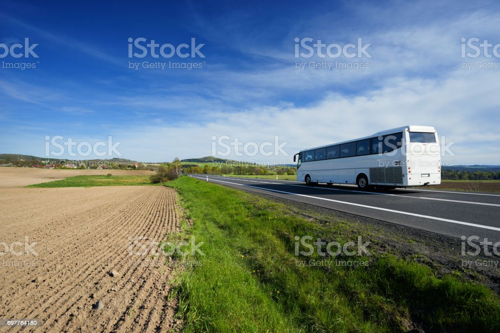 White bus traveling on the road in a rural landscape stock photo