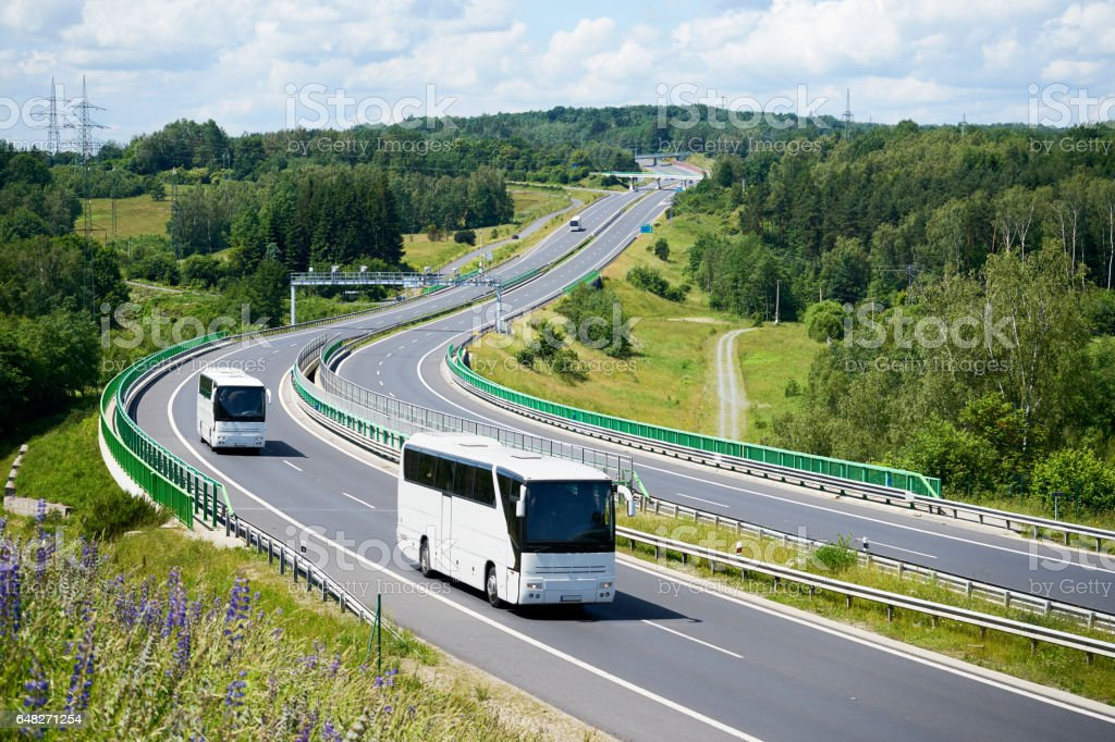 White buses driving on the highway winding through forested areas....