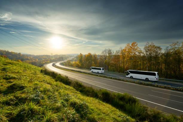 Autobuses blanco por la autopista girando hacia el horizonte en un paisaje de otoño al ponerse el sol - foto de stock