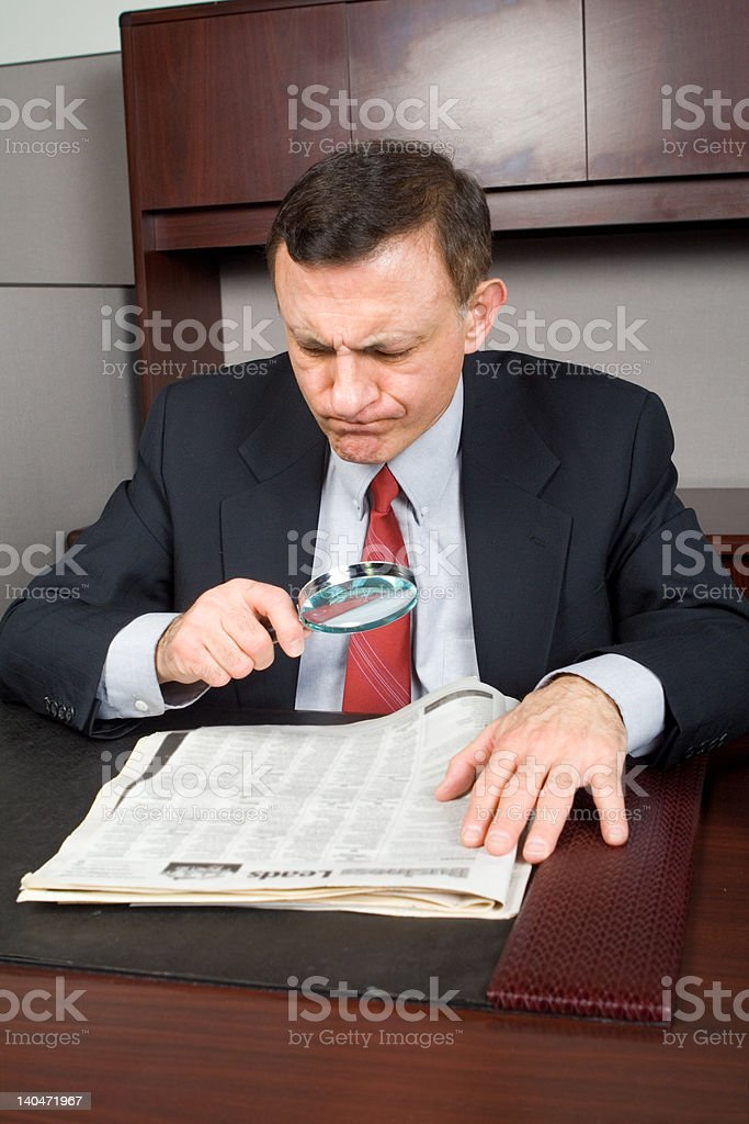 White Businessman Searching Through Newspaper Magnifying Glass Frustrated Expression royalty-free stock photo