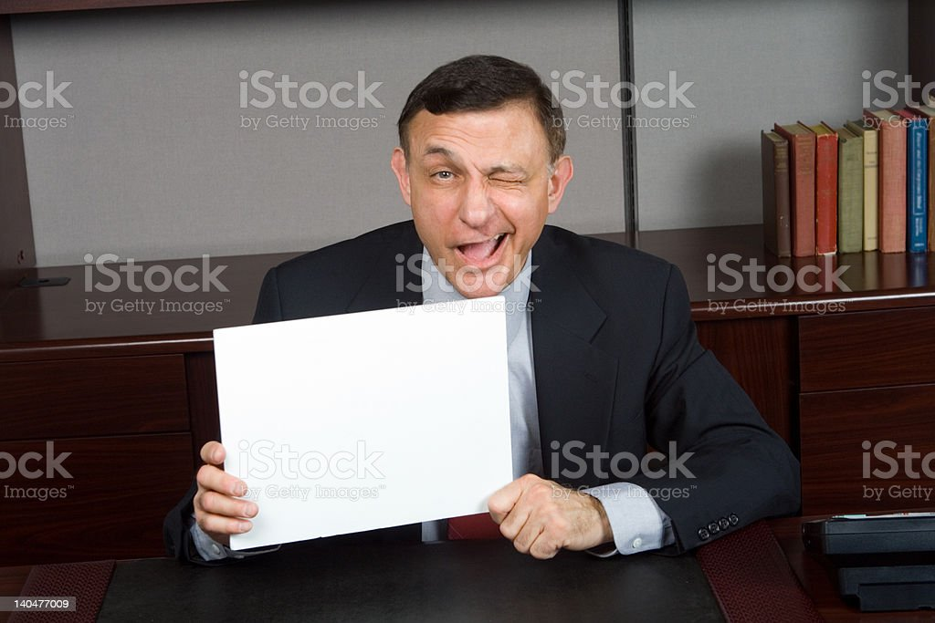 White Businessman Winking at Camera Holding Blank Sign royalty-free stock photo