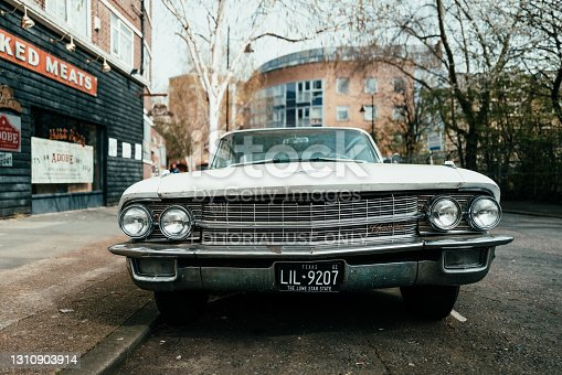 London, UK - 1 April, 2021: an old vintage white Cadillac car parked on a residential city street in London, UK.