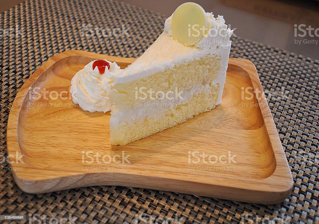 Bolo branco em madeira o delicioso prato. - foto de acervo