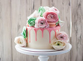 istock White cake with pink melted chocolate, meringues, macaroons and fresh flowers. Rustic background. 1241134530