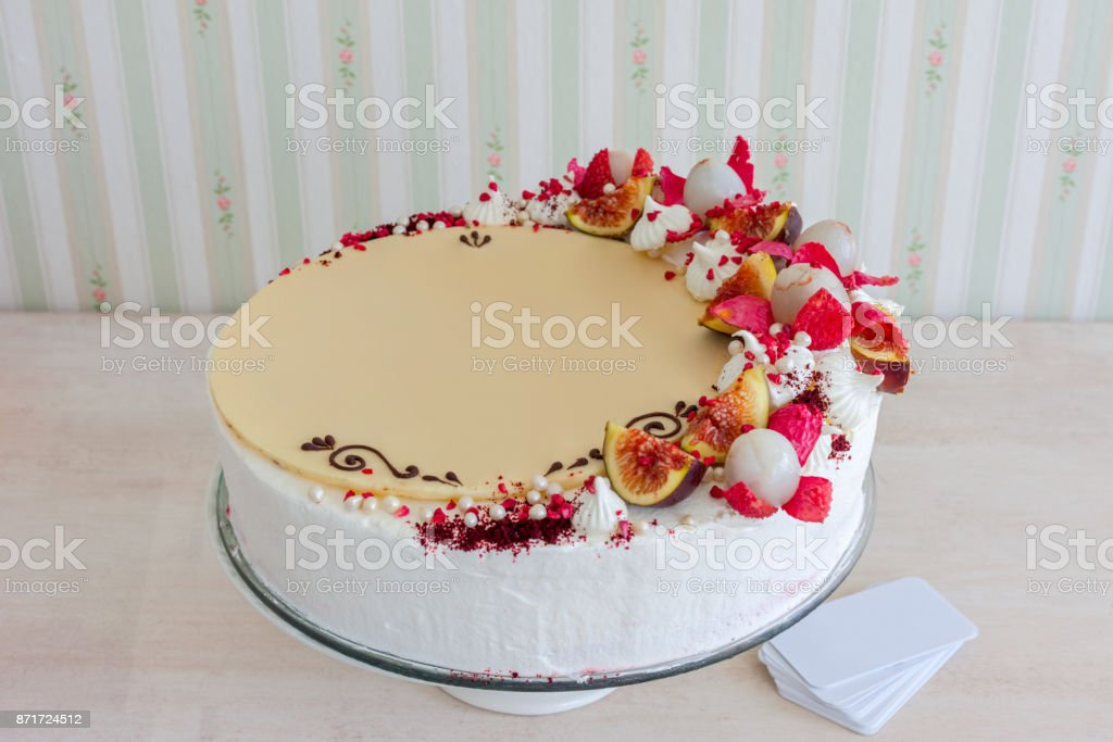 White cake with white chocolate on the wall interior background. stock photo