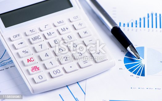 851244800istockphoto White calculator and report with chart and graph, concept of annual financial profit overview, banking and investment, copy space, macro, close up 1158595961