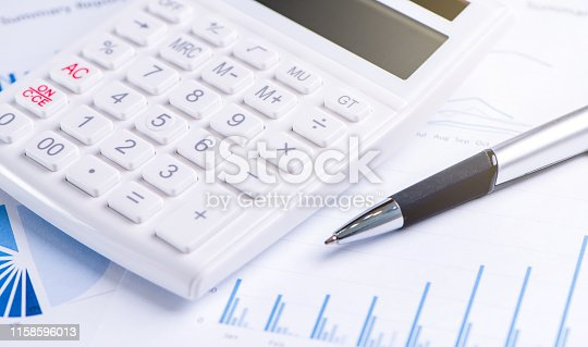 851244800istockphoto White calculator and report with chart and graph, concept of annual financial profit overview, banking and investment, copy space, macro, close up 1158596013