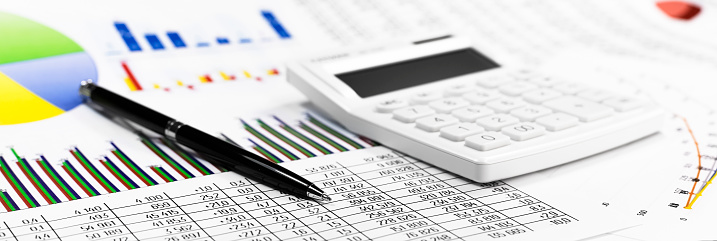 White calculator, coins and black pen on against the background of documents. Financial bookkeeping, Accounting Concept. Top view. Banner.