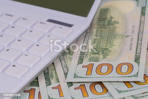 1145921132istockphoto white calculator on 100 dollars banknotes 1094951446