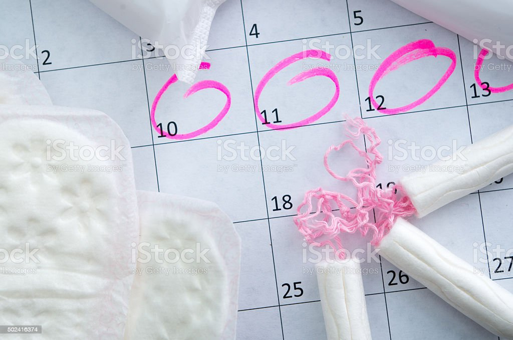 White calendar with pink circles around menstruation date period and stock photo