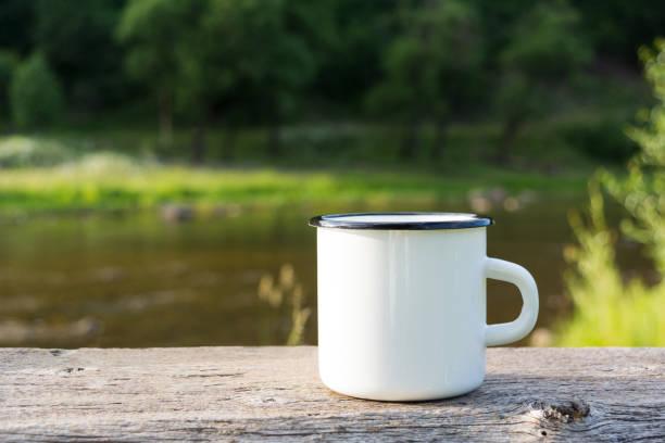 White campfire enamel mug mockup river view stock photo