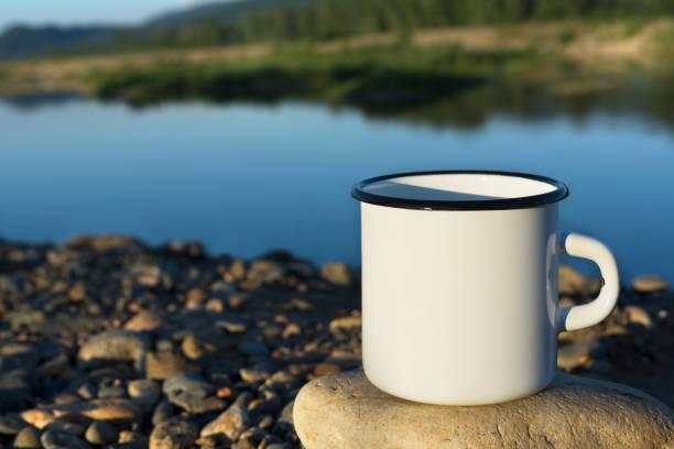 White campfire enamel mug mockup with blue river stock photo