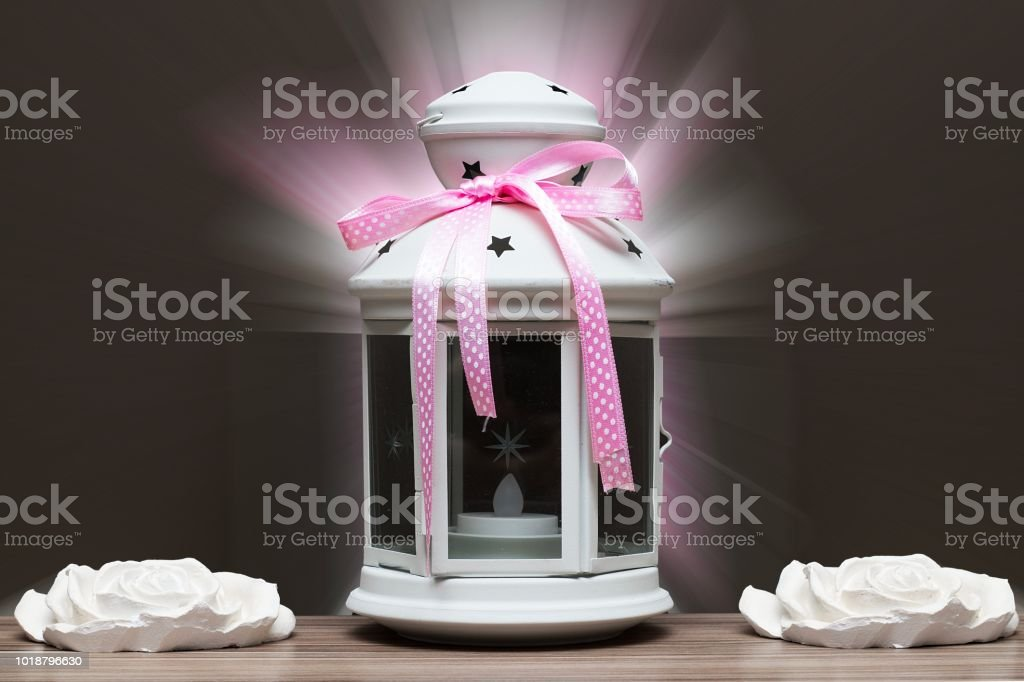 White candile with pink ribbon and white stone flowers. Gift concept on dark wood background stock photo