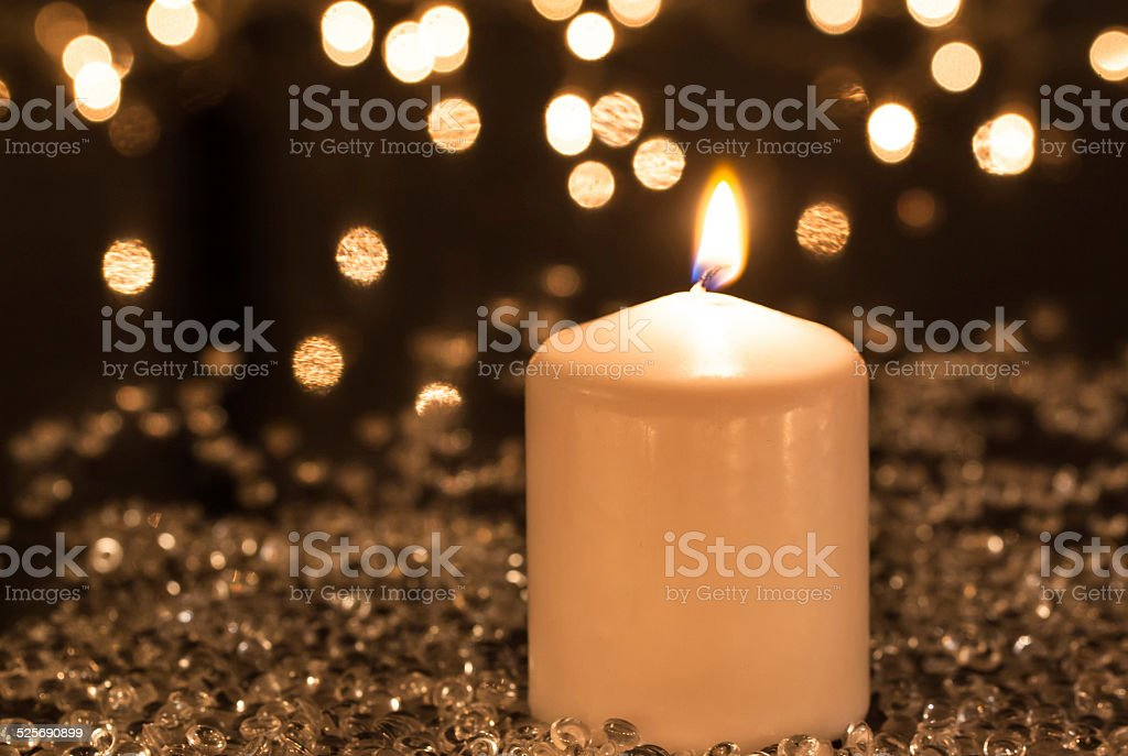 White candle and decorative lights stock photo