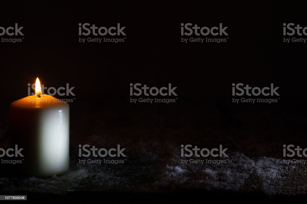 White candle in the night on wooden snowy board christmas abstract background with copy space stock photo