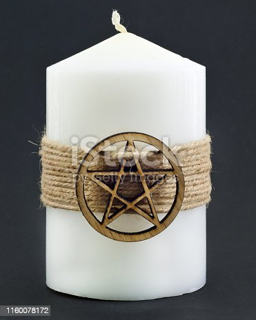 White candle with pentagram on black background