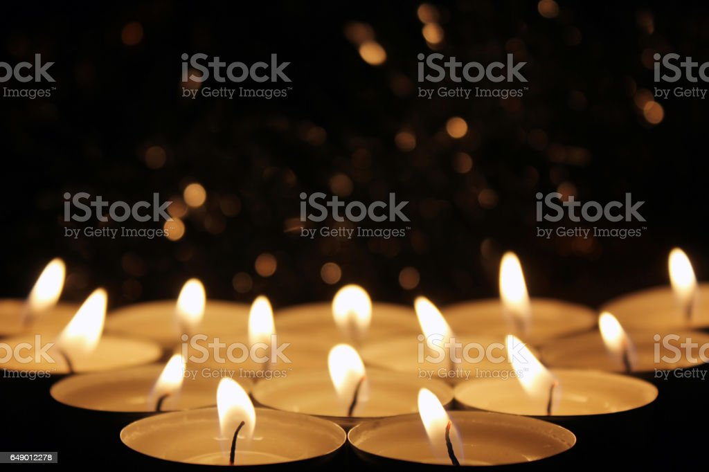 White Candles Burning in the Dark with focus on two candles in foreground. - Photo