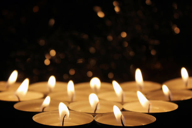 White Candles Burning in the Dark with focus on two candles in foreground. stock photo