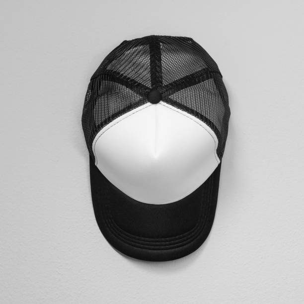 white caps with black nets on cement background. top view angle of baseball cap. - czapka zdjęcia i obrazy z banku zdjęć