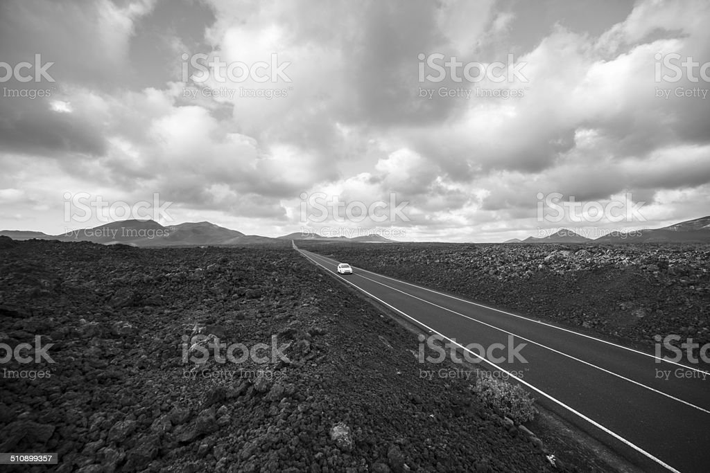 White car on dark road in hostile landscape b&w stock photo
