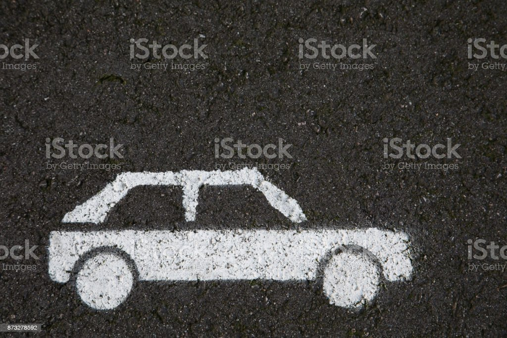 white car is painted on the asphalt on a parking spot