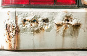White car with rusty and corroded metal peeled paint and holes close up