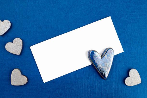 Weiße Karte, ein großes Keramikherz mit blauer Glasur und kleinen Holzherzen auf blauem Hintergrund für Valentinstag-Design, Grüße, Liebeserklärungen – Foto