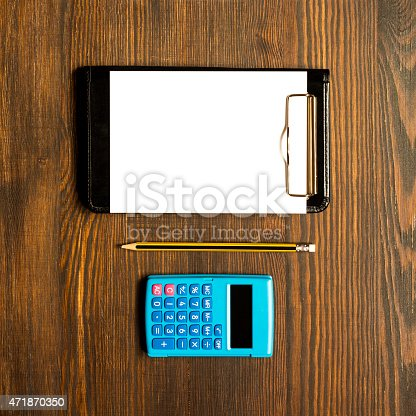 istock White card notebook on wooden desk with pencil and calculator 471870350