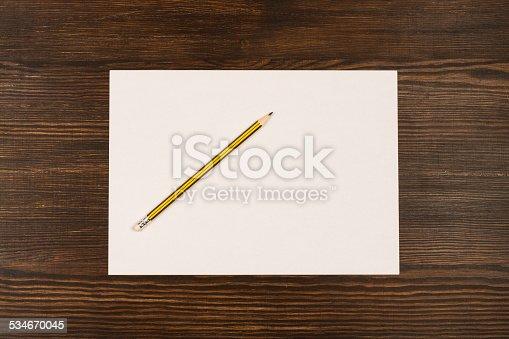 istock White card on wooden desk 534670045
