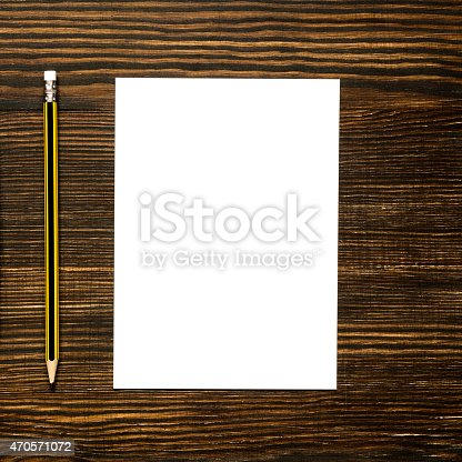 istock White card paper on wooden desk with pencil 470571072