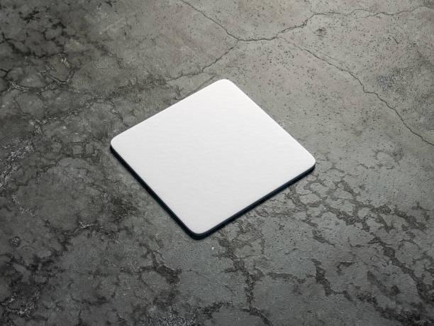 weißer karton quadratische bierdeckel mock-up auf dem betonboden - untersetzer stock-fotos und bilder