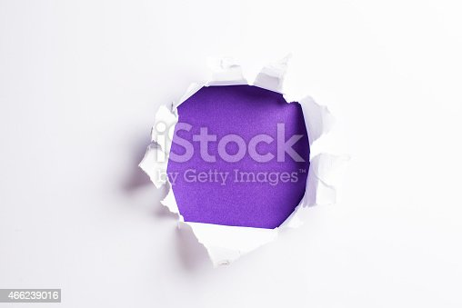 472273278 istock photo White card/paper with torn hole in the middle, colourful background 466239016