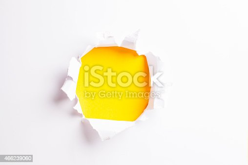 472273278 istock photo White card/paper with torn hole in the middle, colourful background 466239060