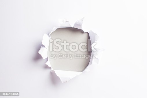 472273278 istock photo White card/paper with torn hole in the middle, colourful background 466239064