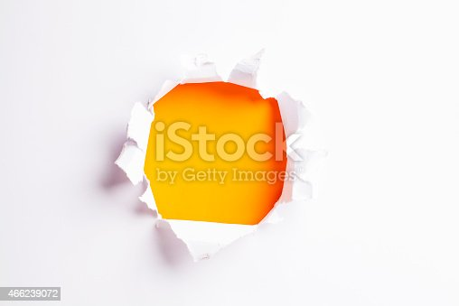 472273278 istock photo White card/paper with torn hole in the middle, colourful background 466239072