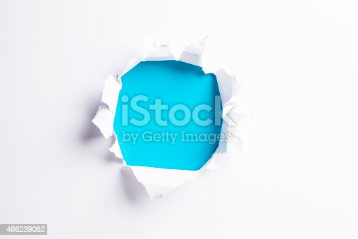 472273278 istock photo White card/paper with torn hole in the middle, colourful background 466239082