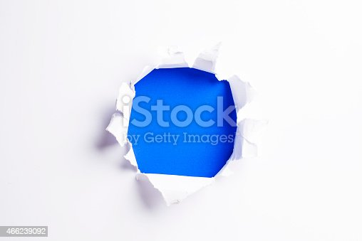 472273278 istock photo White card/paper with torn hole in the middle, colourful background 466239092