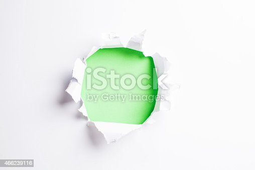 472273278 istock photo White card/paper with torn hole in the middle, colourful background 466239116