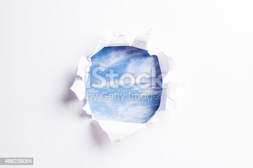 472273278 istock photo White card/paper with torn hole in the middle, sky background 466239054