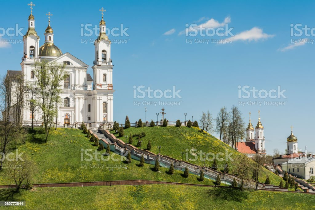 White cathedral with domes is located on the green mountain, on the sides of the stairs are lanterns and coniferous trees grow, near the mountain there are religious buildings, Belarus Vitebsk royalty-free stock photo