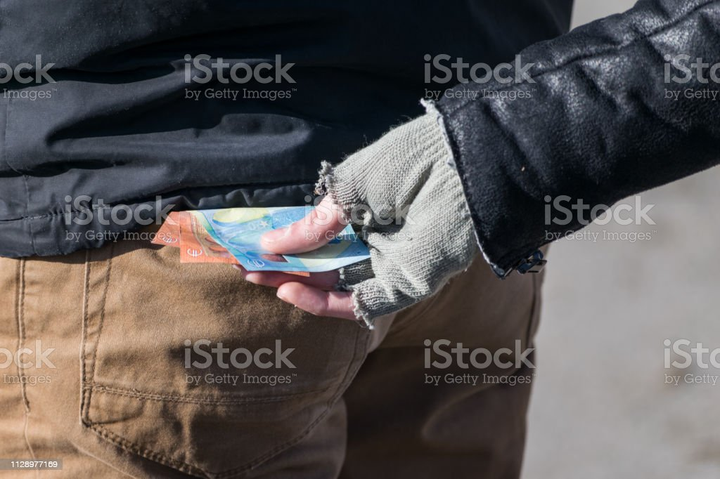 A white Caucasian man with gloves steals money from a black mans back...