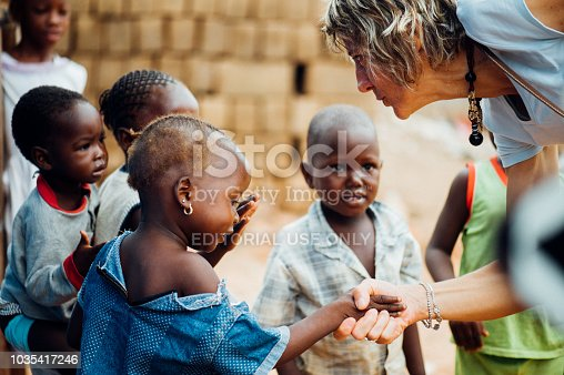 Mali, Africa - circa August 2009 - White caucasian mature woman shaking hands with black african boys in a rural village near Bamako