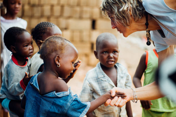 White caucasian mature woman shaking hands with black african people in a rural village Mali, Africa - circa August 2009 - White caucasian mature woman shaking hands with black african boys in a rural village near Bamako developing countries stock pictures, royalty-free photos & images