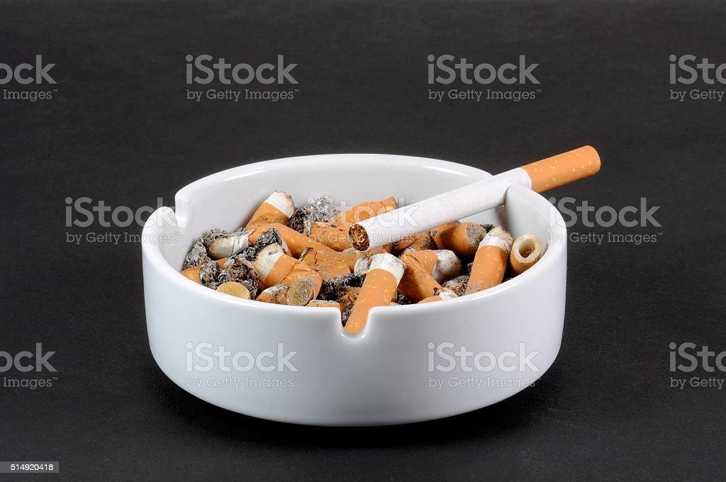 White ceramic ashtray full of smokes cigarettes stock photo