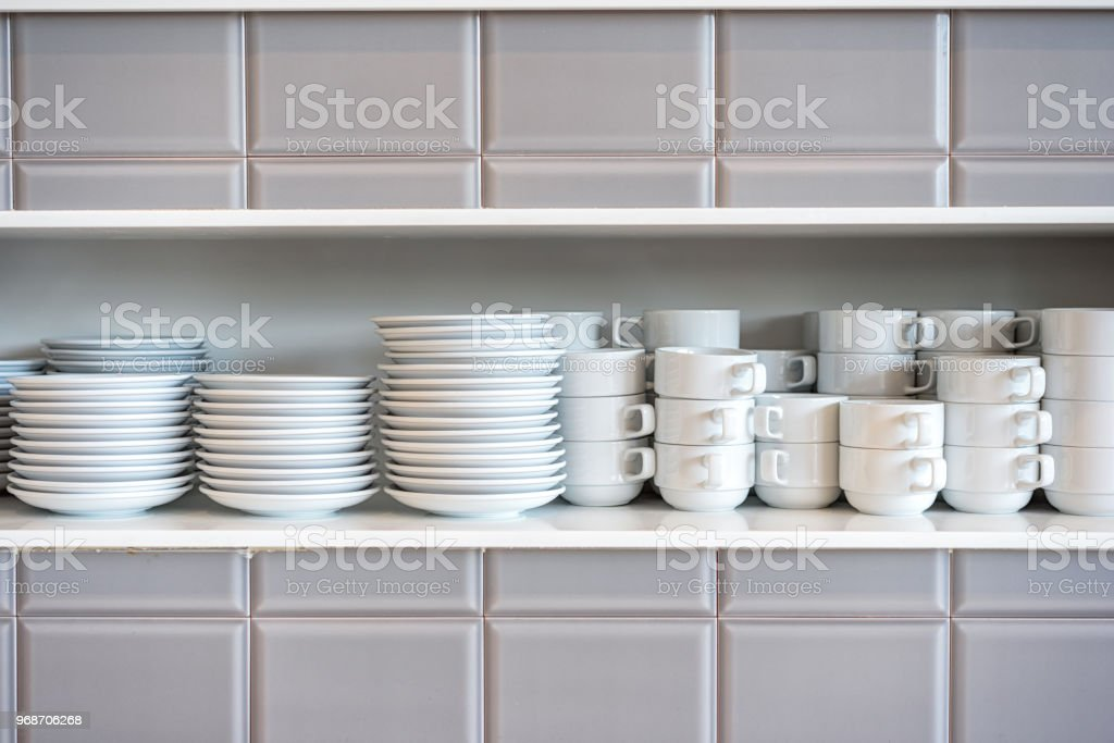 White Ceramic Coffee Cups And Saucers On Restaurant Shelves Shelves With Kitchen Utensils Stock Photo Download Image Now Istock