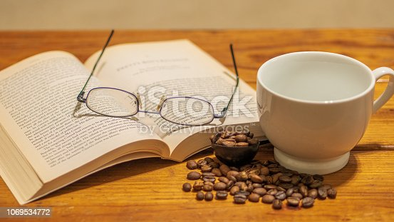 White ceramic empty cup surrounded by small spread of roasted coffee beans, with eye glasses and book atop a wooden coffee table