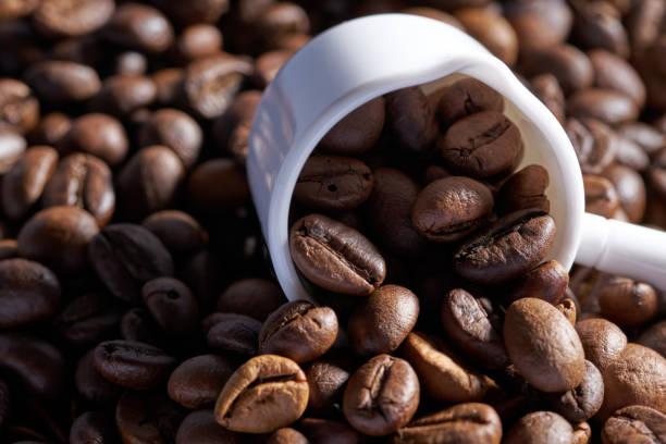 cuchara de medición de cerámica blanca y granos de café, café tostado. de cerca - foto de stock